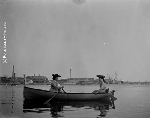 Two women rowing in Piscataqua River with Kittery, Maine shipyard (c) Portsmouth Athenaeum